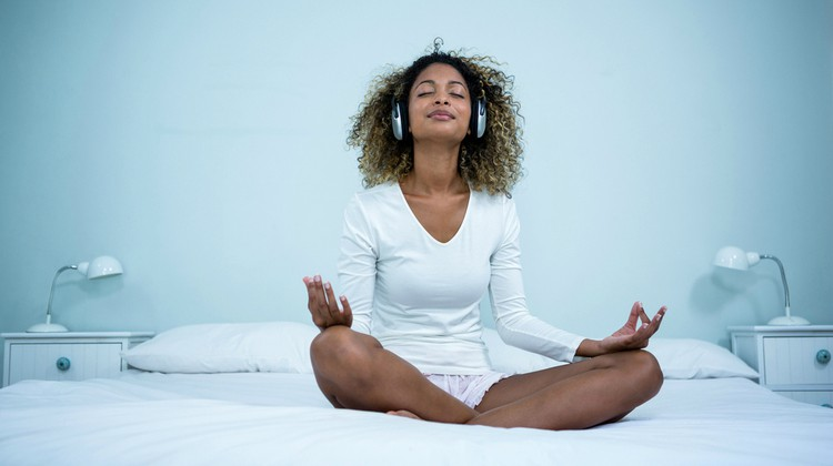 black-woman-meditating-on-bed-with-headphones