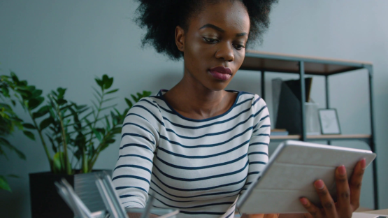 videoblocks-black-african-american-woman-using-laptop-device-at-the-office-woman-holding-tablet-computer-and-reading-close-up_szxlo7khbw_thumbnail-full01
